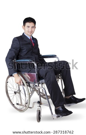 Full length of disabled young businessman wearing formal suit and sitting in the wheelchair - stock photo