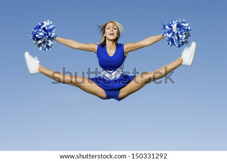 Full length of excited cheerleader with pompoms doing splits against blue sky - stock photo
