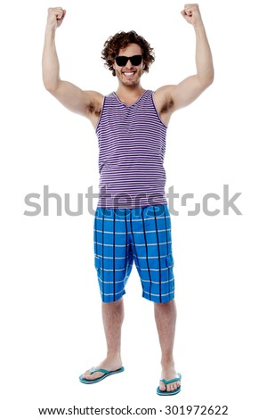 Full length of excited male raising his arm - stock photo
