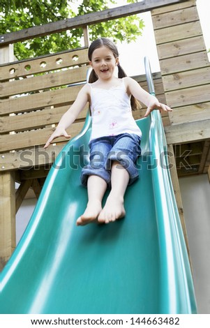 Full length of excited young girl playing on slide in park - stock photo