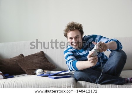 Full length of excited young man playing video game on sofa - stock photo