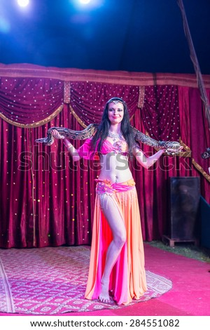 Full Length of Exotic Dark Haired Female Belly Dancer Wearing Bright Pink and Orange Costume with Large Snake Wrapped Around Shoulders on Stage with Red Curtain and Backlit by Bright Spotlights