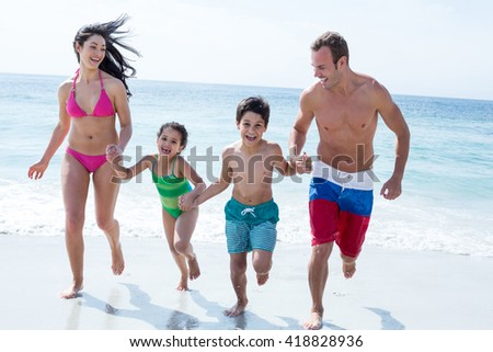 Full length of family running while holding hands on sea shore at beach - stock photo