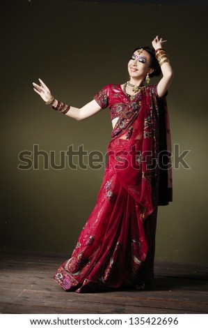Full length of fashion portrait of beautiful female wearing traditional indian costume, posing