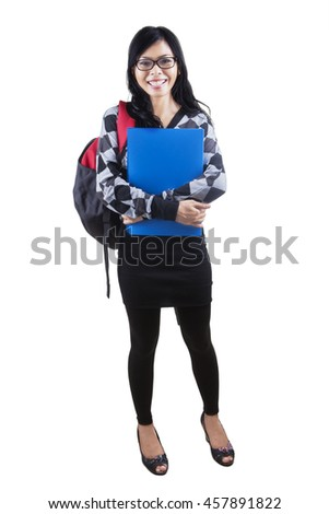Full length of female high school student standing in the studio while carrying bag and smiling at the camera