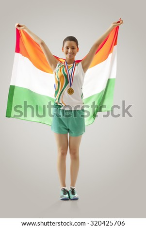 Full length of female medalist celebrating victory with Indian flag against gray background