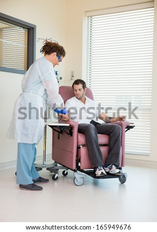Full length of female nurse injecting male patient during chemo treatment - stock photo