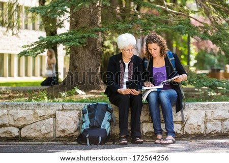 Full length of female student studying on campus with professor helping - stock photo