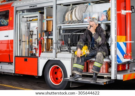 Full length of fireman drinking coffee while sitting in truck at fire station - stock photo
