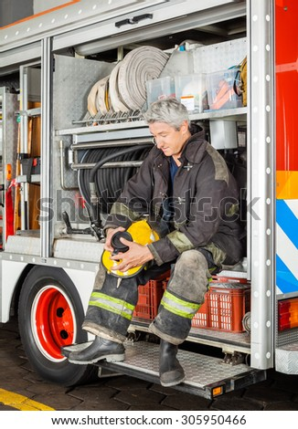 Full length of fireman holding coffee cup while sitting in truck at fire station - stock photo