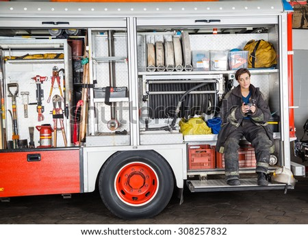 Full length of firewoman holding coffee mug while sitting in truck at fire station - stock photo