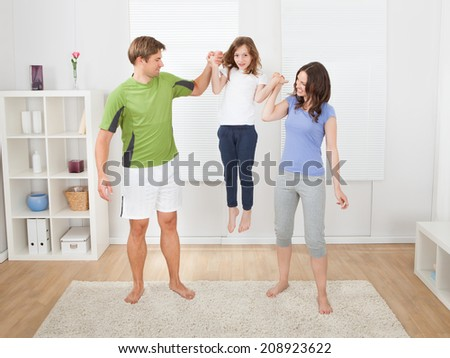 Full length of fit parents picking up daughter while exercising at home - stock photo