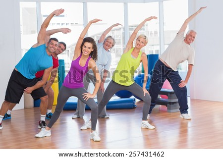 Full length of fit people doing stretching exercise in gym - stock photo