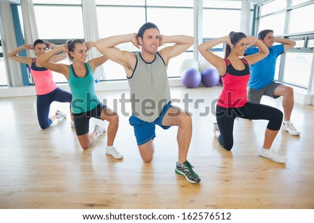 Full length of fitness class and instructor doing pilates exercise in bright room