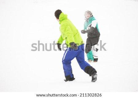 Full length of friends having snowball fight - stock photo