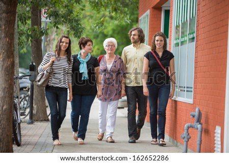 Full length of friends walking together on pavement - stock photo