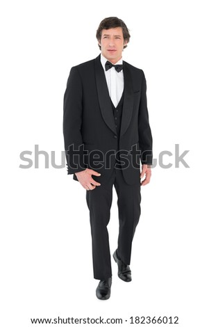 Full length of handsome groom in tuxedo walking over white background