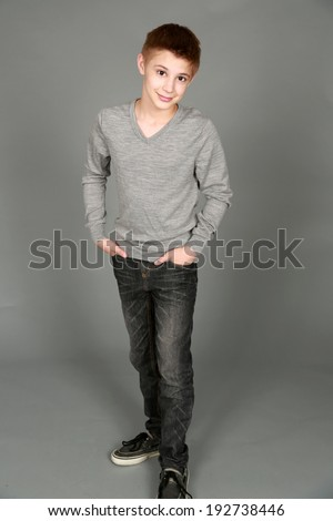 full length of handsome preteen boy looking at camera smiling - stock photo