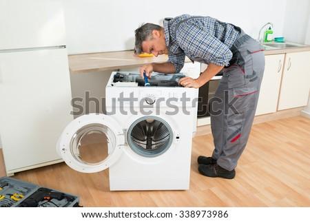 Full length of handyman checking washing machine with flashlight in kitchen - stock photo