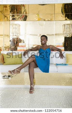 Full length of happy African American woman sitting crossed legs in a lavish store - stock photo