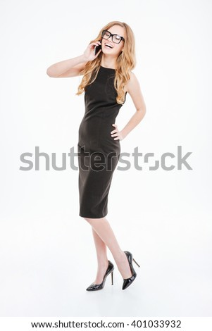 Full length of happy attractive young businesswoman talking on cell phone and laughing over white background  - stock photo