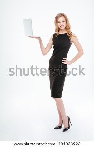 Full length of happy beautiful young businesswoman standing and holding laptop over white background  - stock photo