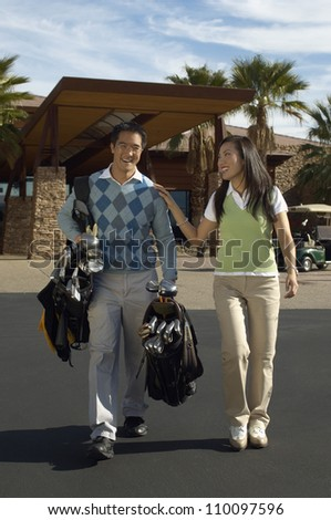 Full length of happy couple carrying golf bags walking out of building - stock photo