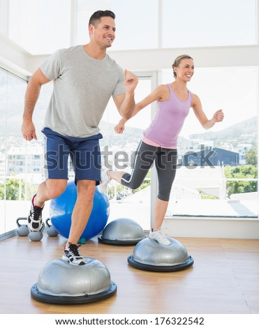 Full length of happy couple doing step aerobics in fitness studio - stock photo