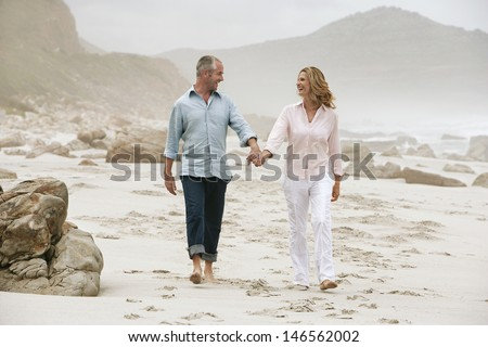Full length of happy couple holding hands while walking on beach - stock photo
