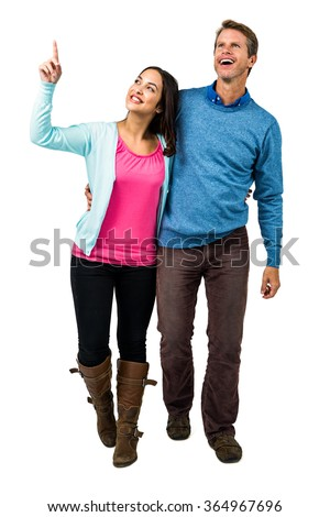 Full length of happy couple looking up while standing against white background - stock photo