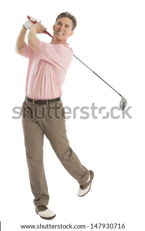 Full length of happy male golfer looking away while swinging golf club isolated on white background - stock photo