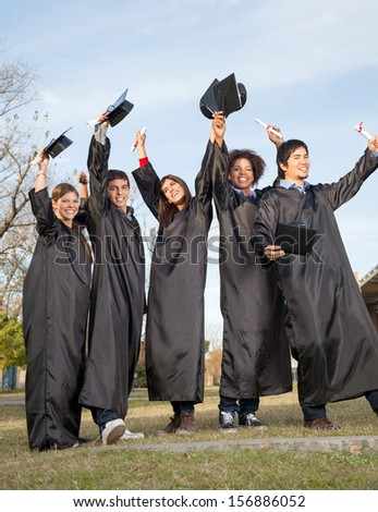 Full length of happy students with diplomas celebrating success on graduation day at college campus - stock photo