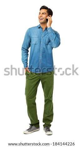 Full length of happy young man answering smart phone over white background. Vertical shot. - stock photo