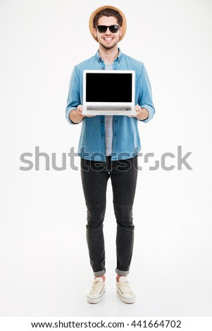 Full length of happy young man in sunglasses and hat holding blank screen laptop - stock photo