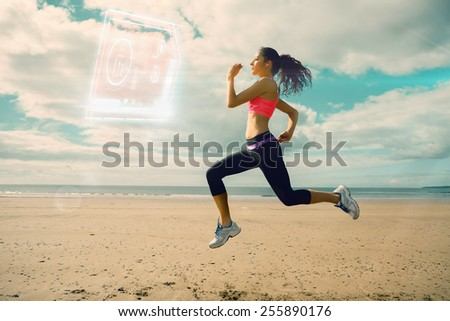 Full length of healthy woman jogging on beach against fitness interface