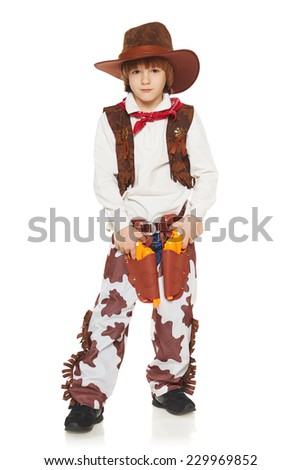 Full length of little boy in a suit of the cowboy posing with guns, on a white background - stock photo