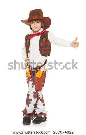 Full length of little boy in a suit of the cowboy showing thumb up sign, on a white background - stock photo