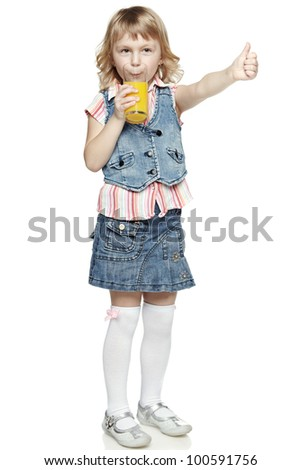 Full length of little girl drinking an orange juice and showing thumb up sign, isolated on white background - stock photo