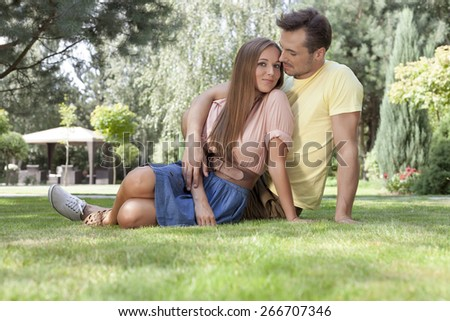 Full length of loving young couple relaxing on grass in park - stock photo