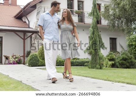 Full length of loving young couple walking on footpath in park - stock photo