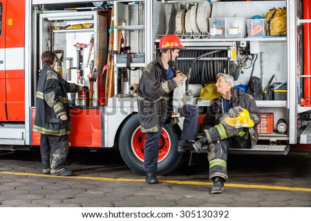 Full length of male firefighters discussing by truck at fire station - stock photo