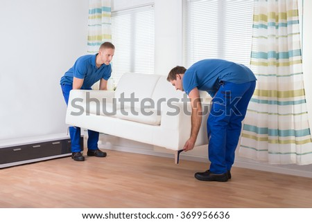 full length of male movers placing sofa on hardwood floor at home