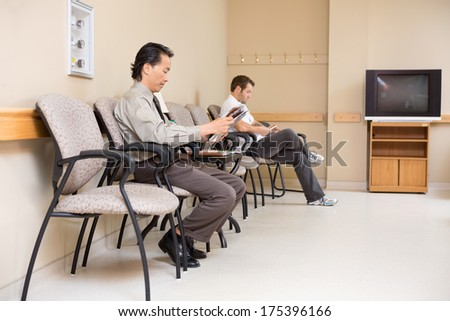 Full length of male patients waiting in hospital lobby - stock photo