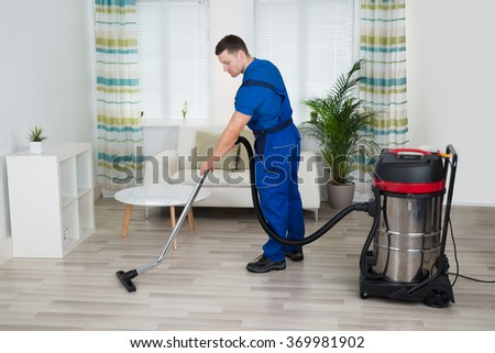 Full length of male worker cleaning floor with vacuum cleaner at home