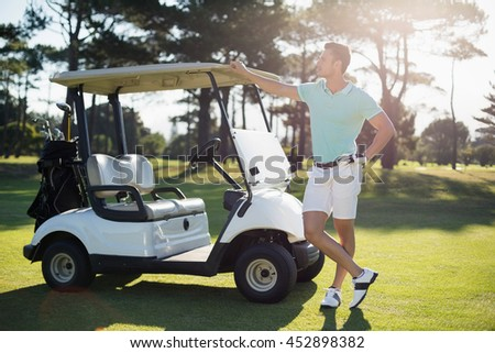 Full length of man by golf buggy on field