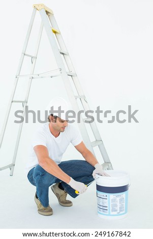 Full length of man crouching while opening paint pot over white background - stock photo