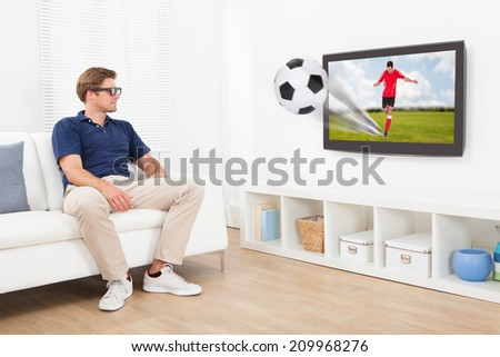 Full length of man in 3D glasses watching football on TV at home - stock photo