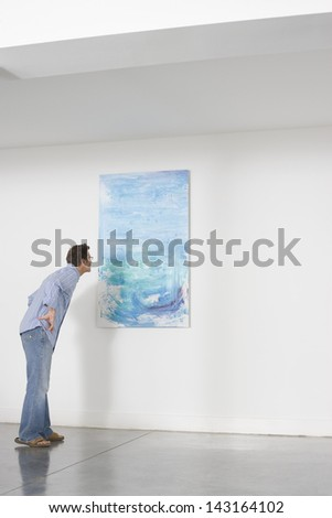 Full length of man observing painting in art gallery - stock photo