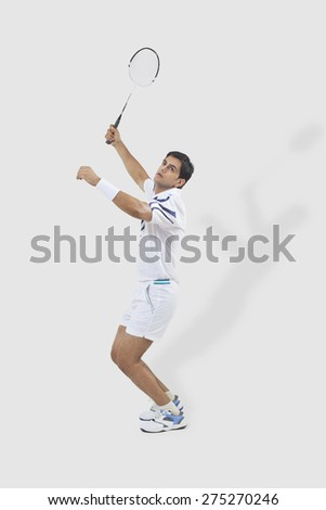 Full length of man playing badminton isolated over white background - stock photo