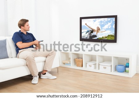 Full length of man watching TV in living room at home - stock photo